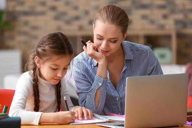 Śliczna dziewczyna z matką odrabia pracę domową w domu