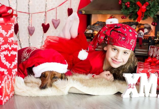 Śliczna dziewczyna z psem leży i uśmiecha się w stroju noworocznym