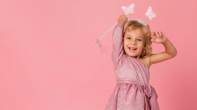 Śliczna dziewczyna z różdżką i kostiumem wróżki