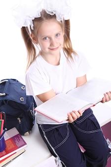 Śliczna dziewczyna z schoolbag obsiadaniem na biurku