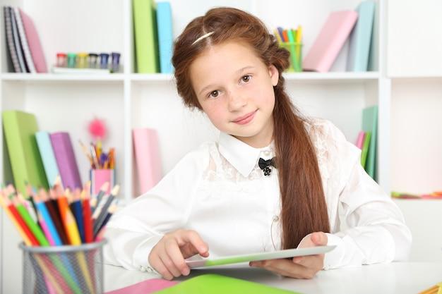 Śliczna dziewczyna z tabletem w miejscu pracy w klasie