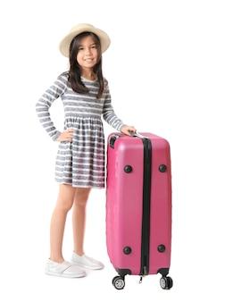 Śliczna dziewczyna z walizką na białej powierzchni