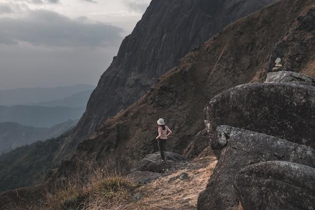Śliczna dziewczyna z wycieczkowiczem podróżnikiem. czerwono-białe paski ustawiają się z tyłu na dużym kamiennym widoku górskim i kopią spodnie. w mulayit taung w myanmarze.