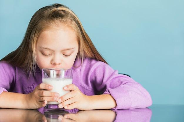 Śliczna dziewczyna z zespołem downa pijąca mleko