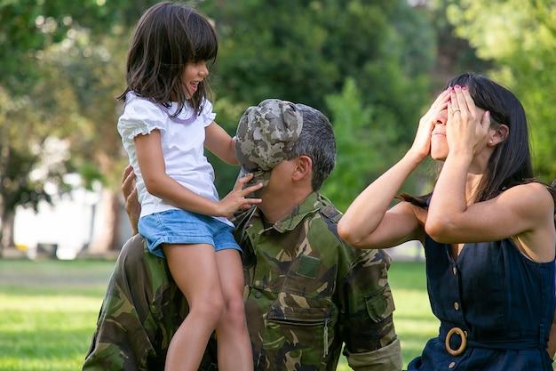 Śliczna dziewczyna zamyka twarz taty z jego czapki. wesoły rodzice bawią się z córką na łonie natury i siedzą z zamkniętymi oczami. szczęśliwa rodzina kaukaski zabawy razem. koncepcja weekendu i rodzicielstwa