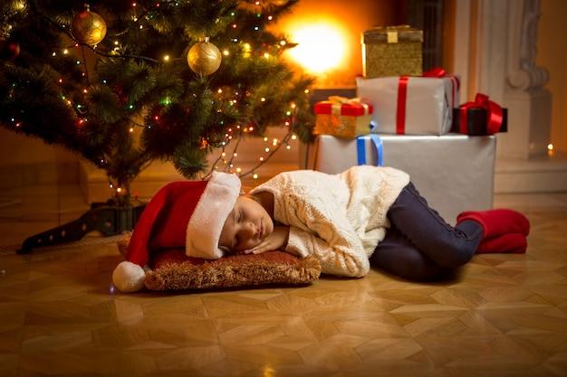 Śliczna dziewczyna zasnęła pod choinką, czekając na świętego mikołaja