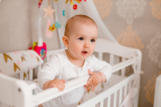 Śliczna dziewczynka 8 miesięcy siedzi w łóżeczku w domu