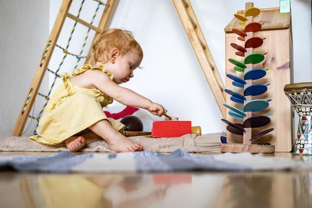Śliczna dziewczynka grająca w drewniane dziecinne ksylofon ekologia zabawki maria montessori materiały