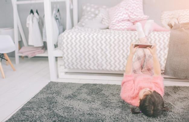 Śliczna dziewczynka grająca w inteligentny telefon, smartfon ma negatywny wpływ na rozwój i zdrowie psychiczne dziecka
