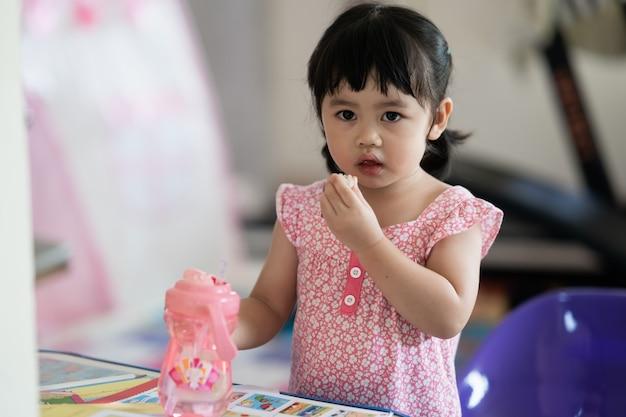 Śliczna dziewczynka je ciasteczka w domu