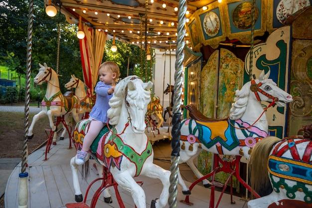 Śliczna dziewczynka na koniu starej karuzeli retro praga czechy