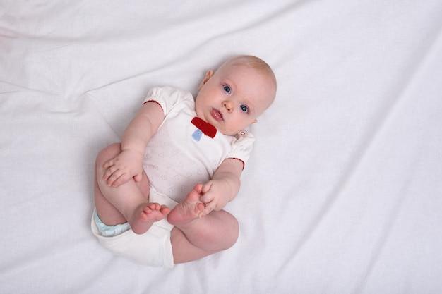 Śliczna dziewczynka noworodka w pieluchach na białych prześcieradłach. widok z góry