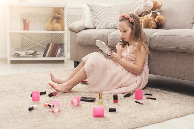 Śliczna dziewczynka próbuje kosmetyków swojej mamy. ładne dziecko siedzi farbując usta szminką, na dywanie podłogowym wśród wielu produktów kosmetycznych. mała fashionistka robi makijaż, kopiuje przestrzeń