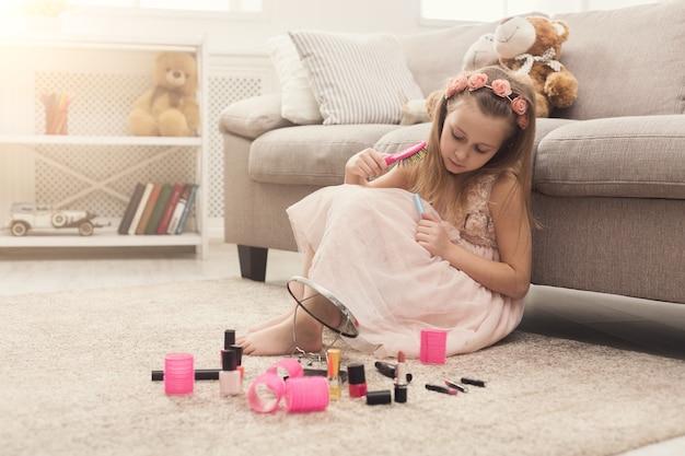 Śliczna dziewczynka próbuje kosmetyków swojej mamy. ładne dziecko siedzi na dywanie podłogowym wśród wielu produktów kosmetycznych. mała fashionistka robi makijaż, kopiuje przestrzeń