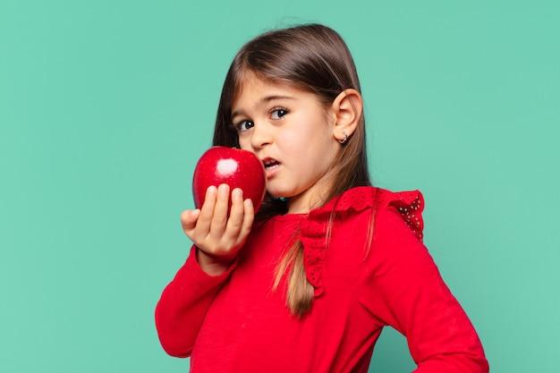 Śliczna dziewczynka przestraszona wyrazem twarzy i trzymająca jabłko