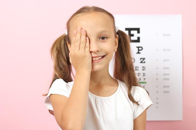Śliczna Dziewczynka Sprawdza Wzrok Za Pomocą Testu Wzroku Okulisty Premium Zdjęcia