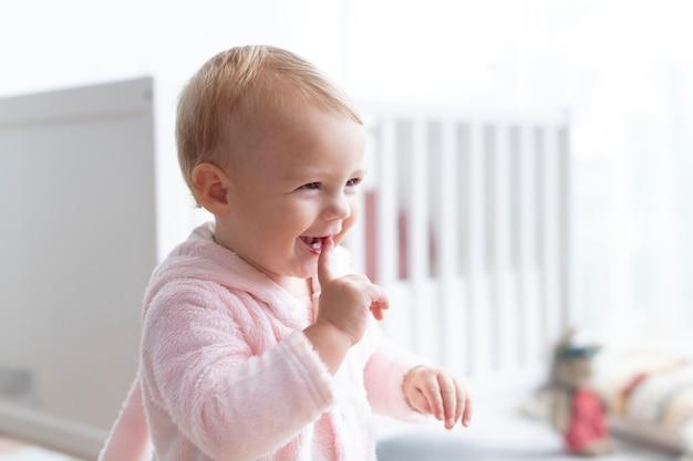 Śliczna dziewczynka uśmiecha się w swoim pokoju dziecinnym