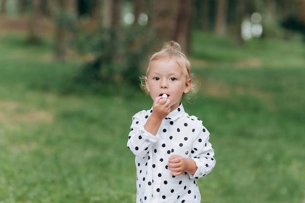 Śliczna dziewczynka uzupełniał pomadką i zabawę w lesie, park. pojęcie wakacji letnich. dzień dziecka. rodzina wspólnie spędza czas na naturze.