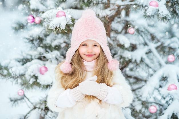 Śliczna dziewczynka w białym futrze i różowej puszystej spódnicy w lesie w zimie ubiera choinkę. różowe świąteczne zabawki.