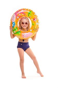 Śliczna dziewczynka w czerwonym bikini w paski, niebieskich spodniach, okularach przeciwsłonecznych i różowym stojaku z wieńcem z gumowym pierścieniem w dłoni