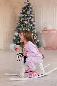 Śliczna dziewczynka w różowej piżamce raduje się prezentem od mikołaja z drewnianego konika na biegunach