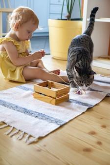 Śliczna dziewczynka w sukience bawi się leżąc na podłodze z kotem grającym w drewniane zdejmowane koraliki
