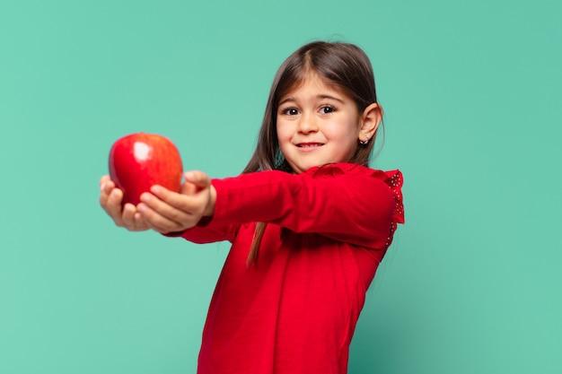 Śliczna dziewczynka wątpi lub niepewny wyraz twarzy i trzyma jabłko