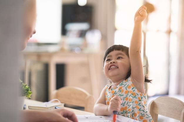 Śliczna dziewczynka z azji rysuje białym papierem na drewnianym stole w domu z matką