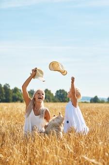 Śliczna dziewczynka z mamą i psem na polu pszenicy. szczęśliwa młoda rodzina spędza razem czas na łonie natury