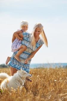 Śliczna dziewczynka z mamą i psem na polu pszenicy