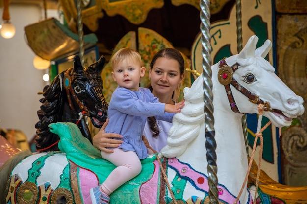 Śliczna dziewczynka z matką na koniu starej karuzeli retro praga czechy