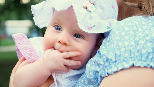 Śliczna dziewczynka z niebieskimi oczami w panamie rozgląda się i ssie palec siedzący w ramionach blond matki pod wiosennym światłem słonecznym z bliska