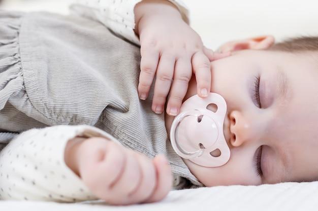 Śliczna dziewczynka ze smoczkiem śpiąca nad białą narzutą
