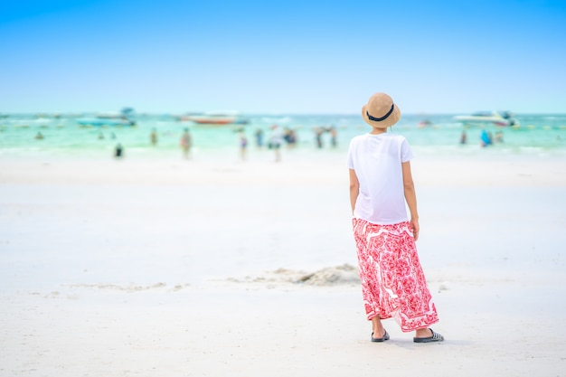 Śliczna dziewczyny pozycja na białym piasku dla relaksującego czasu w lecie na niebieskim niebie.
