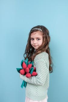 Śliczna dziewczyny pozycja z zabawkarskimi kwiatami