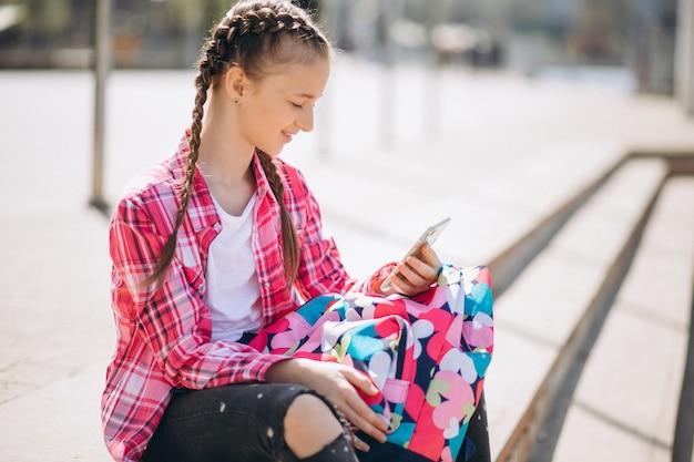 Śliczna dziewczyny rolkowy łyżwiarstwo z telefonem i