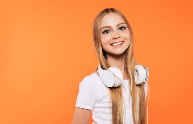 Śliczna emocjonalna mała blondynka w słuchawkach bawi się i tańczy na żółtym tle