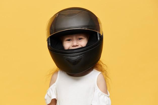 Śliczna figlarna dziewczynka ubrana w czarny kask motocyklowy
