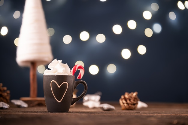Śliczna filiżanka kawy lub gorącej czekolady z czubatą śmietaną w świątecznej dekoracji świątecznej.