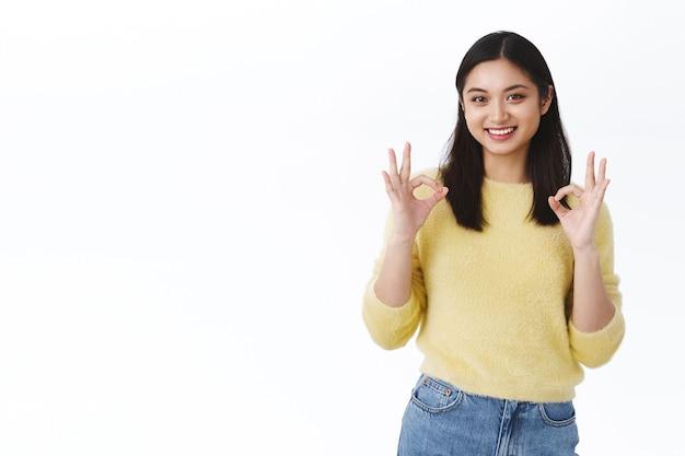 Śliczna i delikatna koreańska dziewczyna zgadza się z tobą, daj pozwolenie. piękna azjatycka kobieta pokazująca dobre gesty i uśmiechająca się, zatwierdzająca wybór, polecająca produkt, zostawiająca pozytywną recenzję, biała ściana