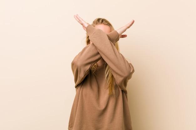 Śliczna i naturalna nastolatek kobieta utrzymuje dwa ręki krzyżować, zaprzecza.
