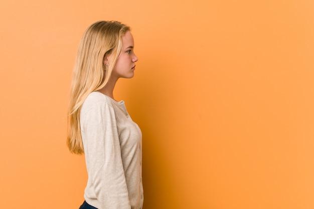 Śliczna i naturalna nastolatek kobieta wpatruje się w lewo, z ukosa poza.