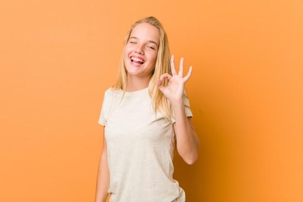 Śliczna i naturalna nastolatka mruga okiem i trzyma w porządku gest ręką.