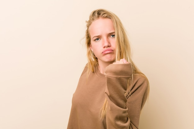 Śliczna i naturalna nastolatka pokazuje pięść do kamery, agresywny wyraz twarzy.