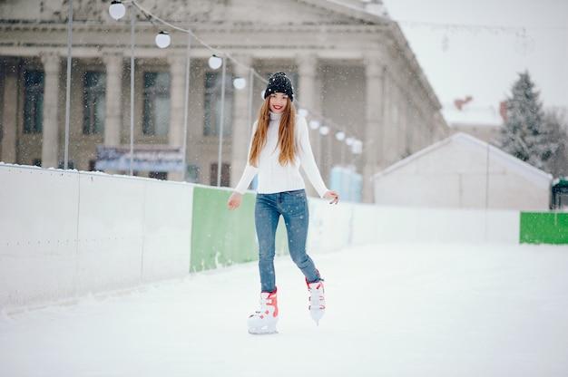 Śliczna i piękna dziewczyna w białym swetrze w zimowym mieście