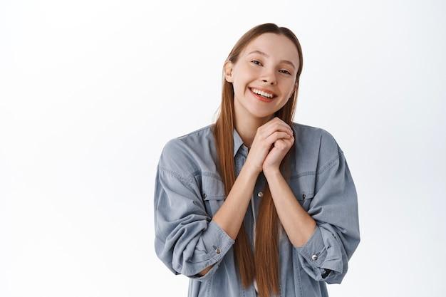 Śliczna i romantyczna dziewczyna, ręce razem, uśmiechnięta i patrząca z podziwu i miłości z przodu, będąca wdzięczna, dziękująca, odbierająca pochwały lub komplementy, pochlebiająca, stojąca nad białą ścianą