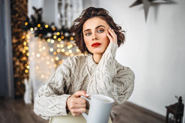 Śliczna i szczęśliwa brunetka siedzi w ciepłym swetrze na krześle, trzymając kubek gorącego napoju