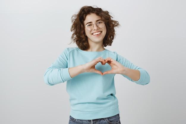 Śliczna i szczęśliwa uśmiechnięta kobieta pokazuje gest serca na klatce piersiowej