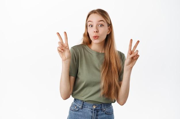 Śliczna i zabawna blond dziewczyna pokazuje pokój w kształcie litery v i pomarszczone usta głupie, stojąc szczęśliwa w letniej koszulce i dżinsach na białej ścianie