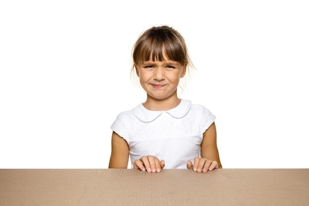 Śliczna i zdenerwowana mała dziewczynka na największej paczce pocztowej. rozczarowana młoda modelka na górze kartonu patrząc do środka.